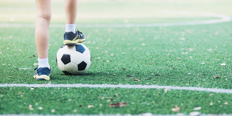 Boy standing with ball in football field ready to start or play new game - sport player concept