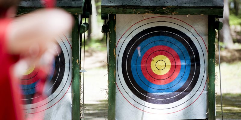 A selective focus shot of a target with a blurred person using bow and arrow